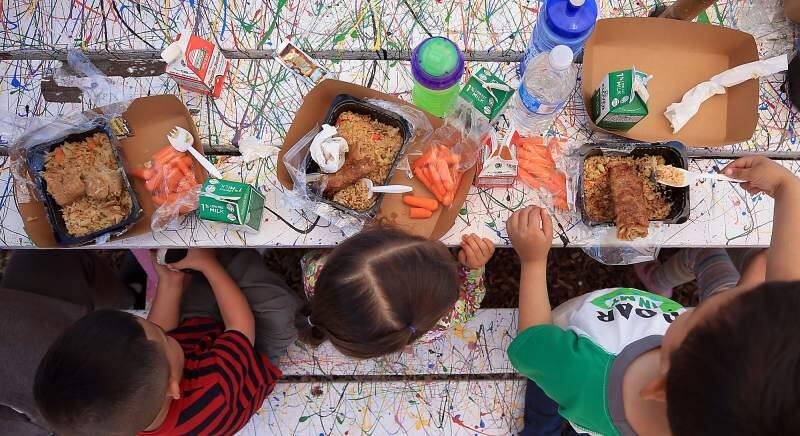 Kent Porter/Press DemocratChildren eat egg rolls and rice with carrots, milk and apple juice from the Redwood Empire Food Bank at Bayer Farm in Santa Rosa in June 2017.
