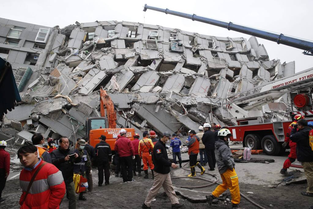 Rescue workers search a collapsed building following a Feb. 6 earthquake in Tainan, Taiwan. (WALLY SANTANA / Associated Press)