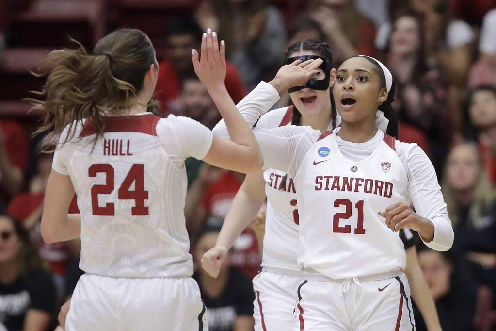 Stanford guard DiJonai Carrington (21) celebrates with forward Lacie Hull (24) and center Shannon Coffee, rear, after scoring against UC Davis during the first half of a first-round game in the NCAA women's college basketball tournament in Stanford, Calif., Saturday, March 23, 2019. (AP Photo/Jeff Chiu)