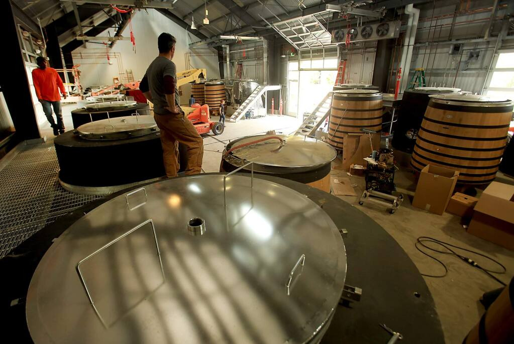 Intern Benny Holland fills a wood tank with water which will be housed with concrete tanks, each weighing in at 13,000 pounds, inside Kosta Browne Winery's Small Lot Fermentation Cellar at the Barlow Center in Sebastopol, Monday August 22, 2016. (Kent Porter / The Press Democrat) 2016