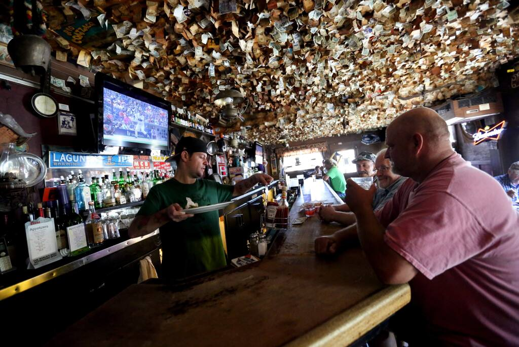 Bartender Ian Avery, left, clears plates from Ken Peters, right, Pete Bacigalupi, second from right and Chuck, third from right at the historic Washoe House on Stony Point Road in Petaluma, Wednesday, July 22, 2015. (CRISTA JEREMIASON / The Press Democrat)