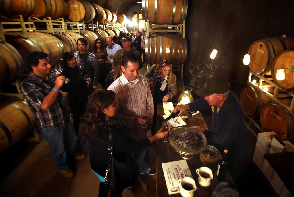 John Duddy serves wine in the caves at Bella Vineyards in the Dry Creek Valley during the annual Wine Road Barrel Tasting in this March 2014 file photo. (JOHN BURGESS/Press Democrat)