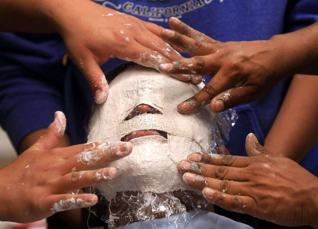 Ivan Villagomez, 16, sits patiently as a mask is made of his face, during the SRJC Native Bridge program, Monday, June 17, 2019 in Santa Rosa. (Kent Porter / The Press Democrat) 2019-