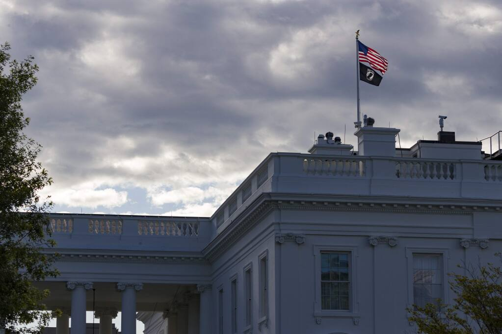 The U.S. flag and the POW-MIA flag fly over the White House on Flag Day, Friday, June 14, 2019, in Washington. (AP Photo/Alex Brandon)