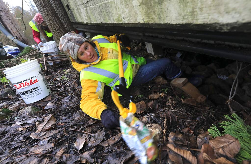 Volunteer Debbie Grima-Lowe climbs under the Guerneville foot bridge to collect trash left after the flooding of the Russian River last week. (John Burgess/The Press Democrat)