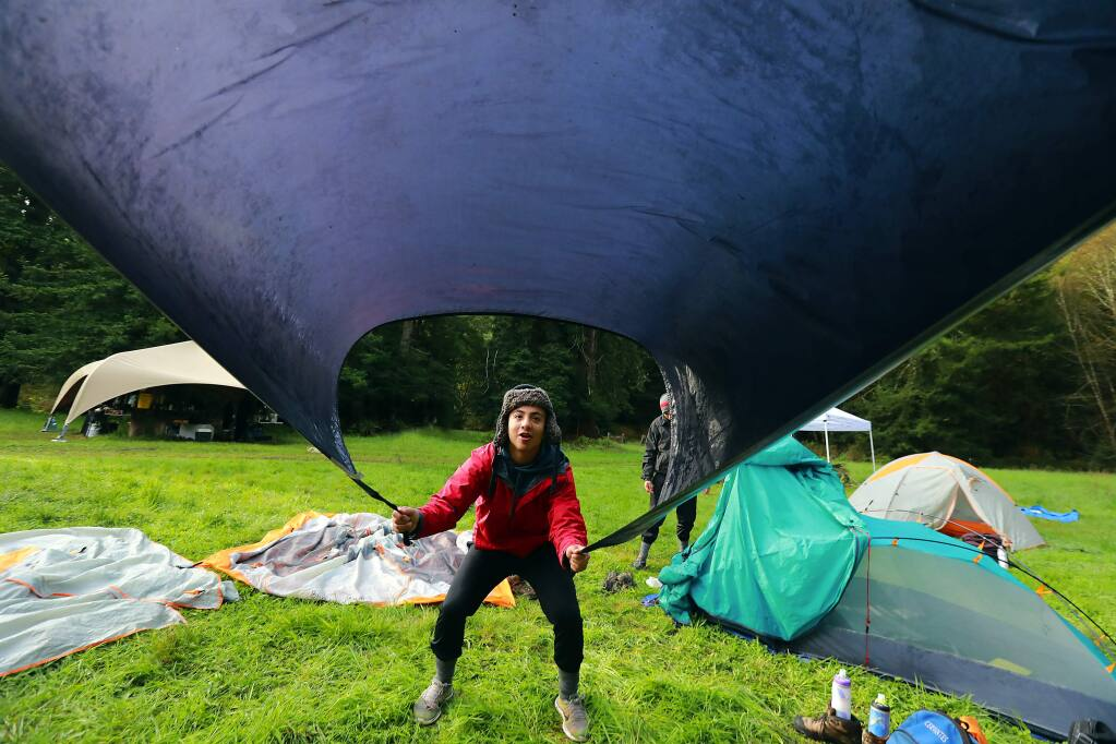 Jorge Cervantes shakes the dew from the tent rainfly before setting off to hike the last 5 miles of their 4 day trek to the ocean with the Inspired Forward program sponsored by LandPaths. (John Burgess/The Press Democrat)