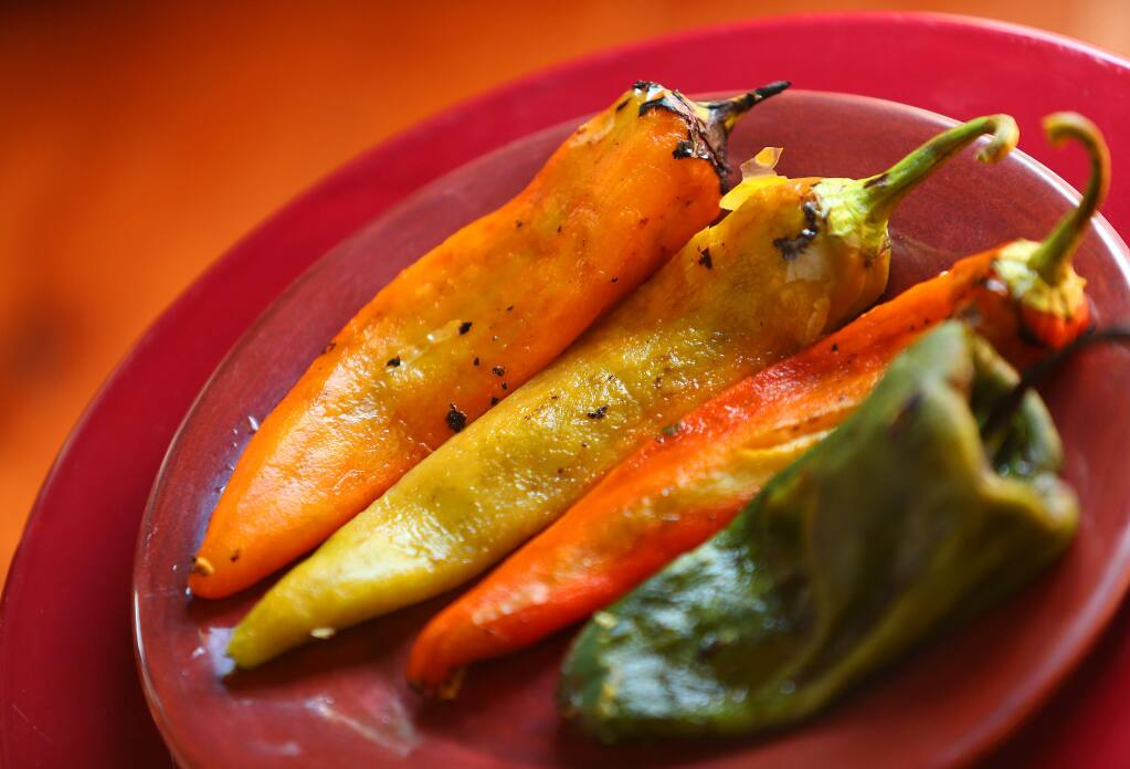 Seared and peeled New Mexico chiles, three on left, and a Poblano chili. (CHRISTOPHER CHUNG/ PD)