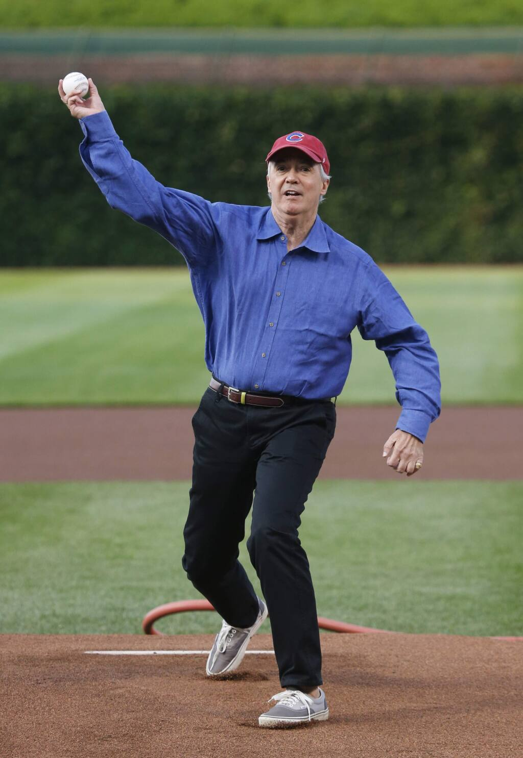 NPR reporter Scott Simon throws out a ceremonial first pitch before a baseball game between the Chicago Cubs and the Colorado Rockies Monday, July 28, 2014, in Chicago. (AP Photo/Charles Rex Arbogast)