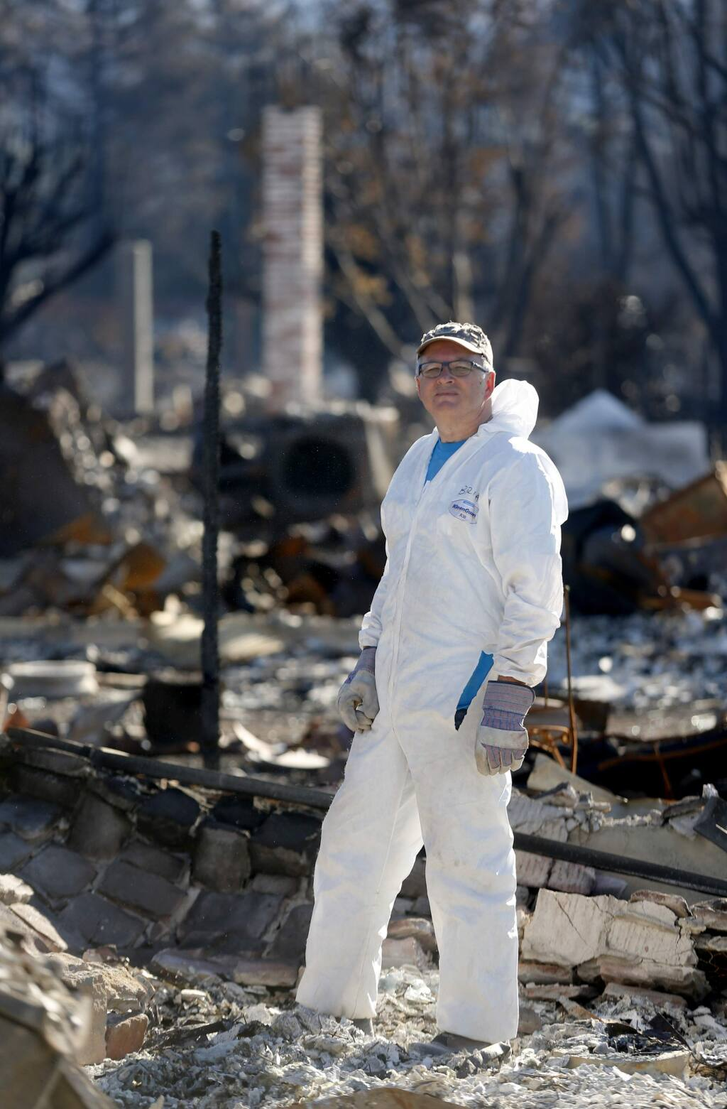 Cartoonist Brian Fies poses for a portrait while looking through the rubble of his home in Mark West Estates in the Larkfield-Wikiup area of Santa Rosa, on Wednesday, October 25, 2017. (BETH SCHLANKER/ The Press Democrat)