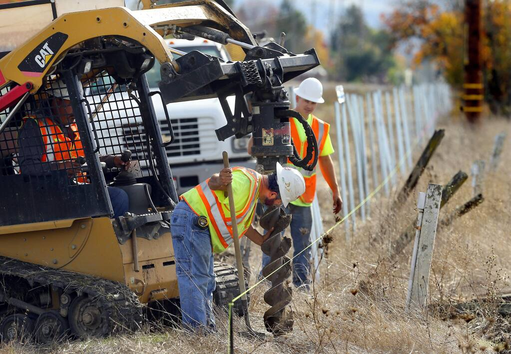 Hector Garcia, left, and Josh Cox dig holes for poles for a fence along the SMART tracks north of San Miguel Rd. in Santa rosa on Wednesday. (JOHN BURGESS / The Press Democrat)