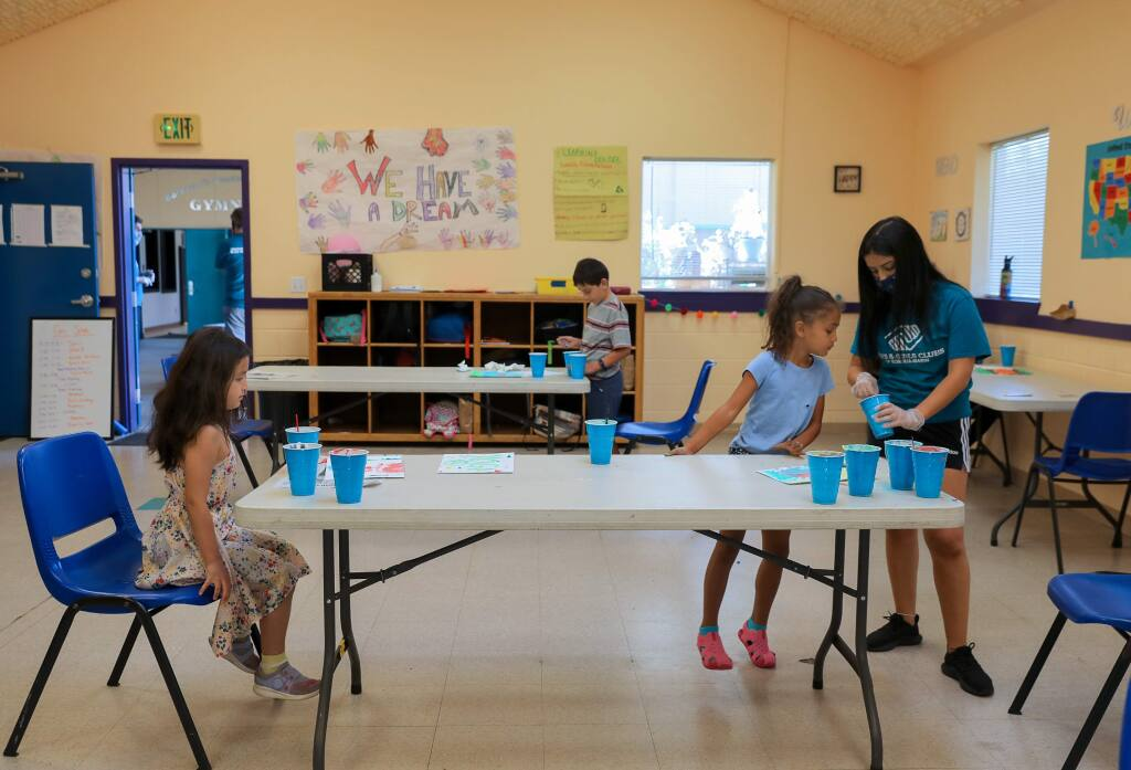 Brianna Farasat, right, helps Jealyn Fuller, 5, to make puffy paint, while separated Izilda Vicente, 6, sits at the other end of the table at the Boys & Girls Club, in Windsor on Monday, June 8, 2020. All staff members wear face masks, and campers are kept at the proper social distance.(Christopher Chung/ The Press Democrat)