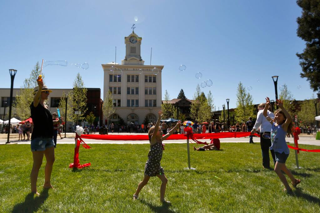 Dawn Sanz, left, floats bubbles in the breeze for her daughters Lily, 5, and Charlee, 8, during the celebration of the reunified Old Courthouse Square, in Santa Rosa, California, on Saturday, April 29, 2017. (Alvin Jornada / The Press Democrat)