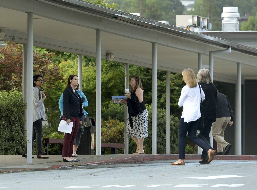 Novato High School staff members arrive at work Thursday, May 26, 2016, following at attack on two students. Attackers shot two students Wednesday near the San Francisco Bay Area high school, killing one and sending another to a hospital in an incident that prompted the closing of the campus to students. (Robert Tong/Marin Independent Journal via AP)