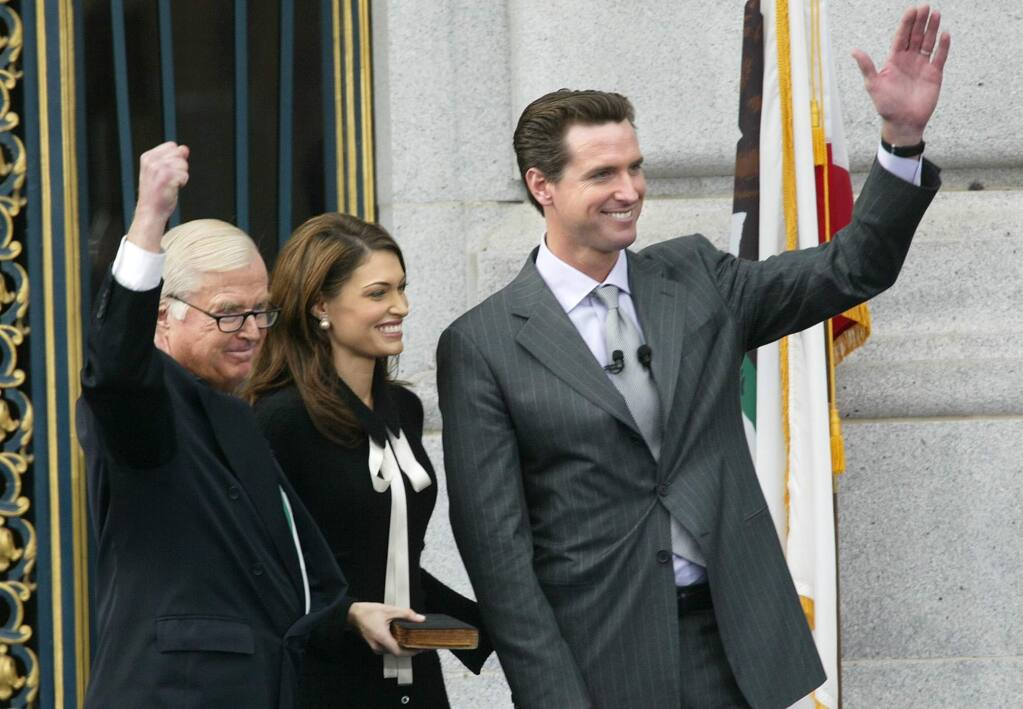 FILE - In this Jan. 8, 2004, file photo, newly sworn-in San Francisco Mayor Gavin Newsom, right, waves to supporters after taking the oath of office from his father, Judge William Newsom, left, at City Hall in San Francisco. At center is Kimberly Newsom, the mayor's wife. William Newsom III, a former California judge, has died at age 84. A Gavin Newsom spokesman says William Newsom died Wednesday morning, Dec. 12, 2018, at his home in San Francisco. (AP Photo/Jeff Chiu, File)