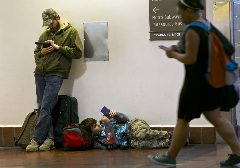 Passengers Morgan Griffin, 20, left, and his brother, Eric Crandell 12, browse their mobile devices as they await to board The Amtrak Pacific Surfliner train bound to Santa Barbara, Calif., at Union Station in Los Angeles, Wednesday, Nov. 26, 2014, a day before Thanksgiving. (AP Photo/Damian Dovarganes)