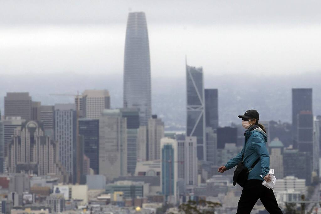 A woman wears a mask during the coronavirus outbreak while crossing a street in front of the skyline in San Francisco, Saturday, April 4, 2020. (AP Photo/Jeff Chiu)
