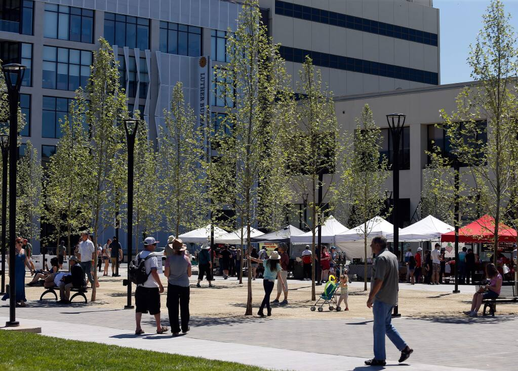 People mill around the new trees during the celebration of the reunified Old Courthouse Square in Santa Rosa, California, on Saturday, April 29, 2017. (ALVIN JORNADA/ PD)