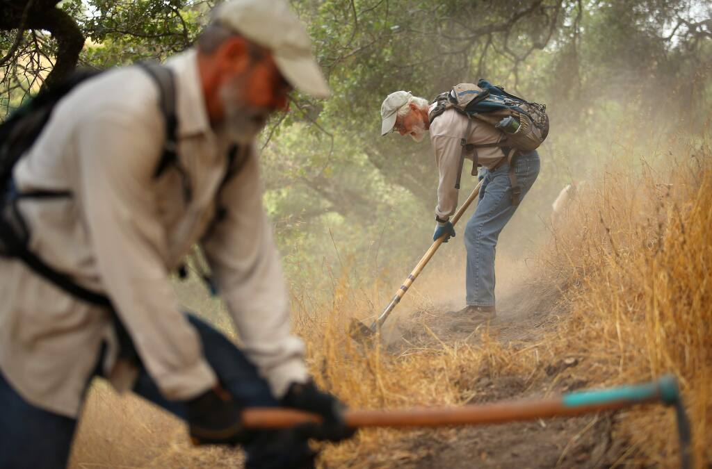 (FILE PHOTO) Tim Mayer, right, and Michael Yares work on cutting a new trail at Taylor Mountain, in Santa Rosa on Wednesday, August 6, 2014. (Christopher Chung/ The Press Democrat)
