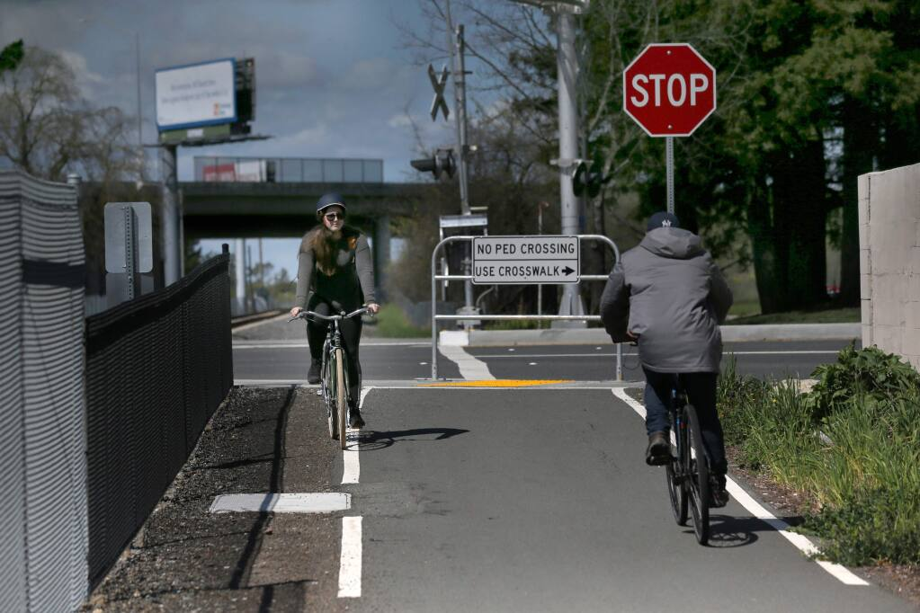 Emily Townshend rides her bike at the start of a section of the SMART pathway near Golf Course Dr. in Rohnert Park, California on Thursday, March 21, 2019 .(BETH SCHLANKER/The Press Democrat)
