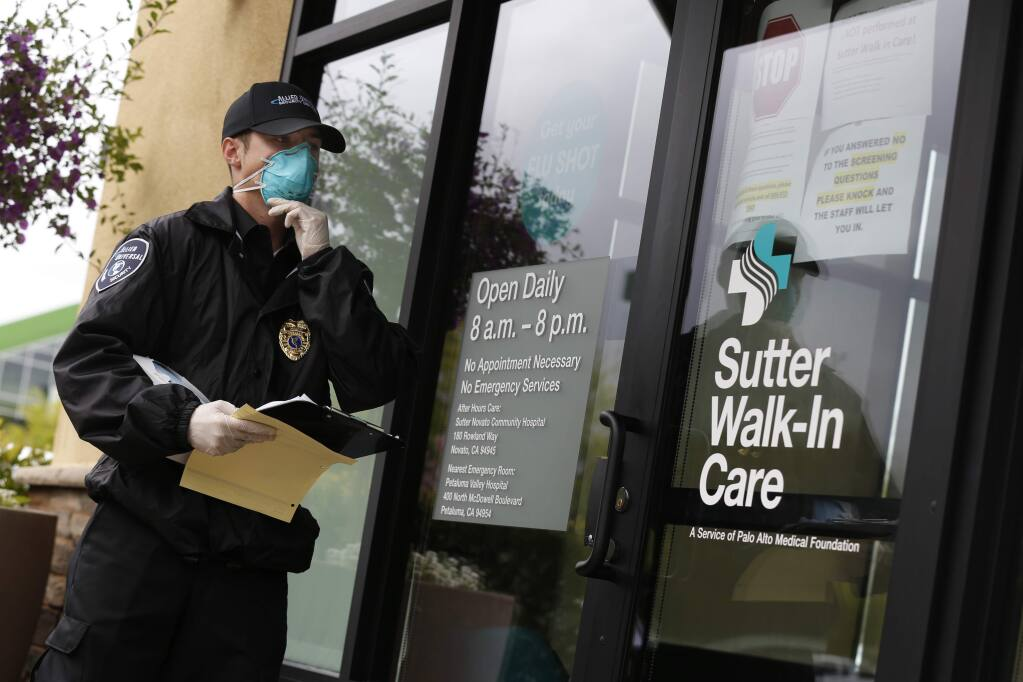 Robert Fletcher, a security guard with Allied Universal, waits with a questionnaire to screen patients about their symptoms before they can enter Sutter Walk-In Care in Petaluma, California on Wednesday, March 18, 2020. (BETH SCHLANKER/The Press Democrat)
