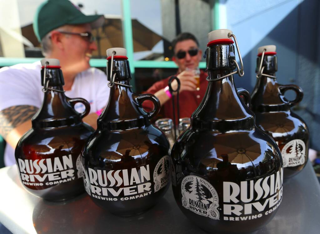 Michael Cole, lett, and Jim O'Connell brought their growlers at the Pliny the Younger release day at Russian River Brewing Company in Santa Rosa on Friday. (JOHN BURGESS / The Press Democrat)