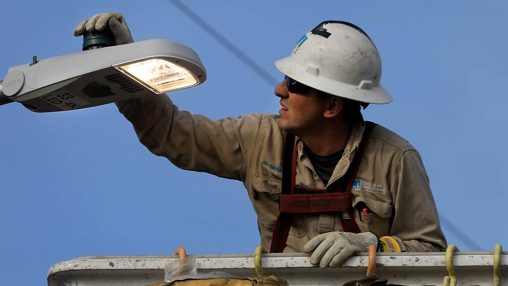 Pacific Gas and Electric apprentice lineman Chris Washington checks to see if a Coffey Park streetlight is operating, Tuesday Dec. 19, 2017. (Kent Porter / The Press Democrat) 2017