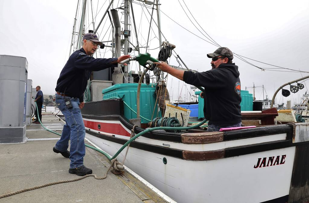 Tom Graham, right, hands a gas pump to Spud Point Marina attendant John Keller, after fueling up the 'Janae', in Bodega Bay on Monday, July 31, 2017. Graham and his brother, Jeff Graham, are heading out for the start of the commercial salmon fishing season.(Christopher Chung/ The Press Democrat)