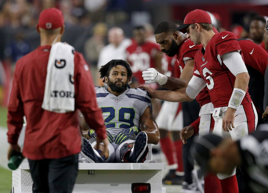 In this Sept. 30, 2018, file photo, Seattle Seahawks defensive back Earl Thomas (29) is greeted by Arizona Cardinals players as he leaves the field after breaking his leg during the second half in Glendale, Ariz. (AP Photo/Ross D. Franklin, File)