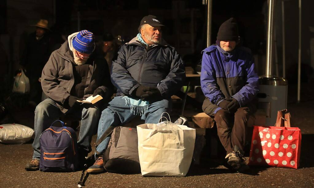 From left, Pete Magoni, Fleming Smith and Robert White, bundled up against the cold, wait for a ride to the Sam Jones Hall shelter, Friday Dec. 25, 2015 at Catholic Charities on Morgan Street in Santa Rosa. (Kent Porter / Press Democrat)