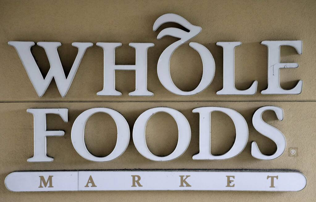 FILE - In this Aug. 28, 2017 file photo, a sign at a Whole Foods Market greets shoppers in Tampa, Fla. The online retailing giant plans to roll out two-hour delivery at the organic grocer this year to those who pay for Amazon's $99-a-year Prime membership. The move is the latest by Amazon to put its stamp on its recent purchase of Whole Foods. (AP Photo/Chris O'Meara, File)