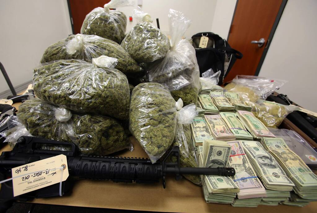 Guns, cash and marijuana seized by authorities in 2013 from a home north of Santa Rosa. (JOHN BURGESS/ PD FILE)