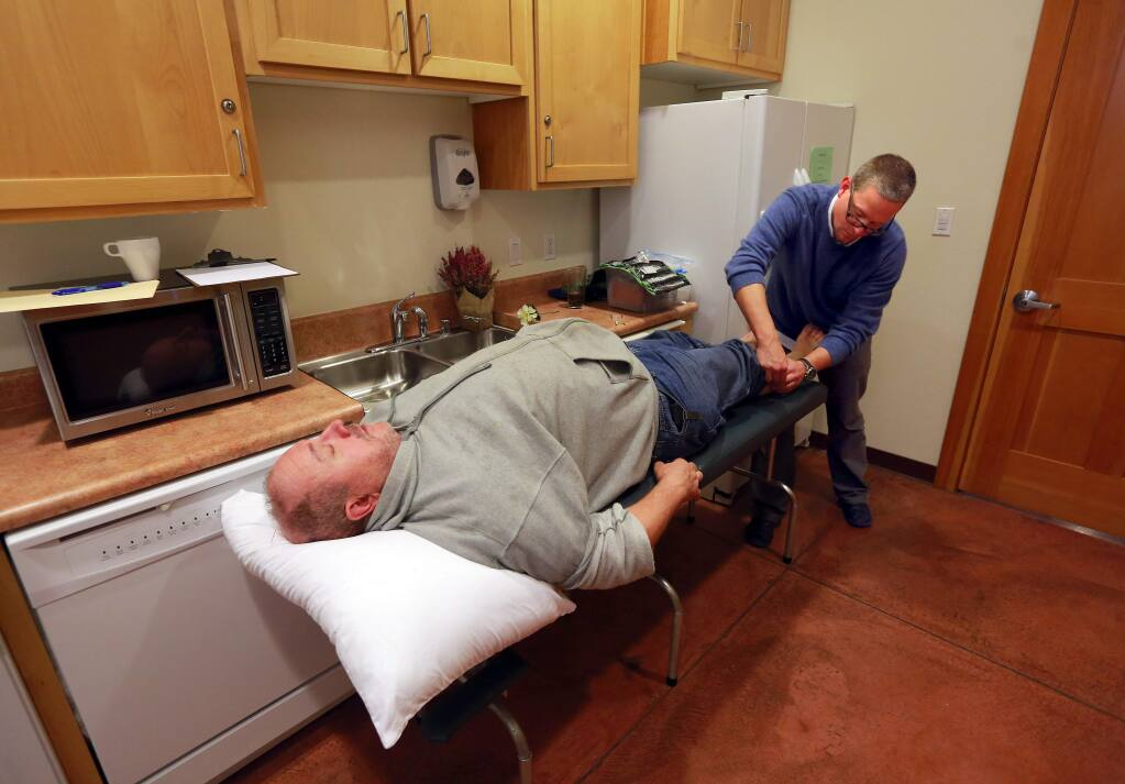 Acupuncturist Graham Lankford used a needle on the calf of Joe Trinidade at the the Community Holistic Clinic a the Colgan Meadows Community Room in Santa Rosa on Friday. (JOHN BURGESS / The Press Democrat)