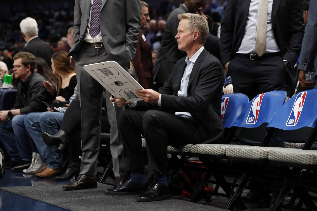 Golden State Warriors head coach Steve Kerr sits on the bench before the start of an NBA basketball game against the Dallas Mavericks in Dallas, Wednesday, Nov. 20, 2019. (AP Photo/Tony Gutierrez)