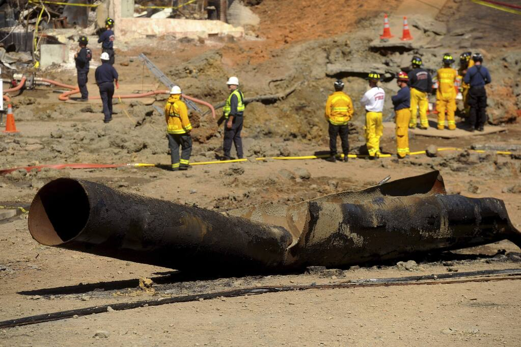 FILE - In this Sept. 11, 2010, file photo, a Pacific Gas & Electric natural gas line lies broken on a San Bruno, Calif., road after a massive explosion. U.S. prosecutors are urging a federal judge to work with a court-appointed monitor to determine ways Pacific Gas & Electric Co. can prevent its equipment from starting more wildfires. In a court filing Wednesday, Jan. 23, 2019, the U.S. attorney's office in San Francisco said Judge William Alsup should refrain from immediately imposing new requirements on the utility. (AP Photo/Noah Berger, File)
