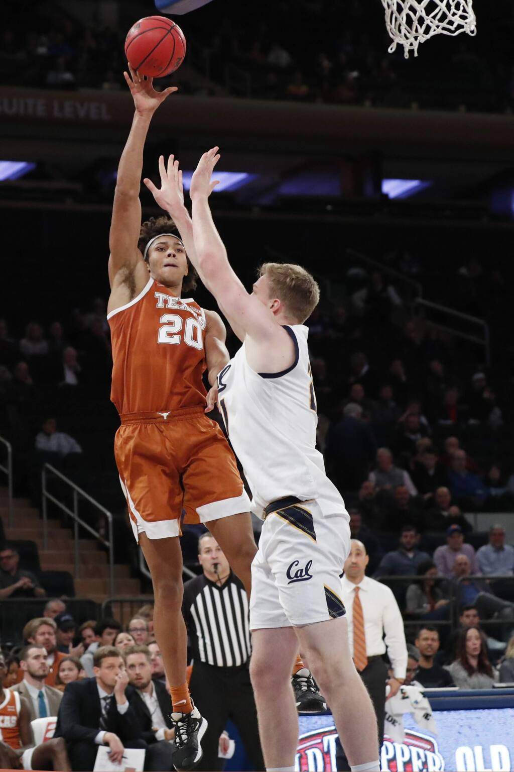 Texas forward Jericho Sims (20) passes around Cal forward Lars Thiemann (21) during the second half in the 2K Empire Classic, Thursday, Nov. 21, 2019, in New York. (AP Photo/Kathy Willens)