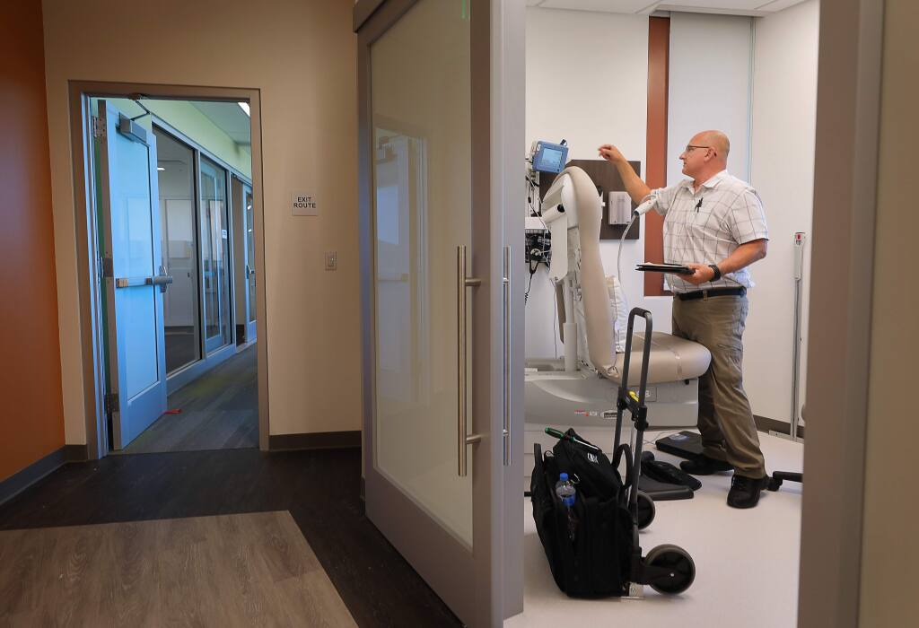 Mike Crenshaw performs electrical safety checks on medical equipment in an examination room at the Santa Rosa Community Health Vista Campus, in Santa Rosa on Tuesday, August 13, 2019. The campus has been closed since it sustained damage in the Tubbs fire(Christopher Chung/ The Press Democrat)
