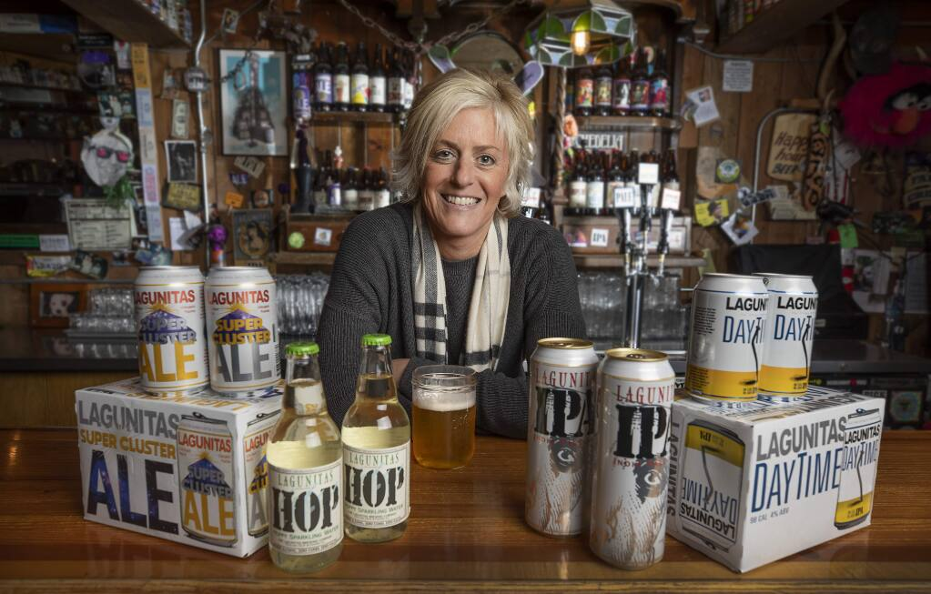 Lagunitas Brewing Co. CEO Maria Stipp with product lines for the Petaluma company, from left, Super Cluster, a citra-hopped mega ale, Hop sparkling water, cans for their flagship IPA and DayTime, a 98-calorie low alcohol IPA. (JOHN BURGESS/ THE PRESS DEMOCRAT, 2019)