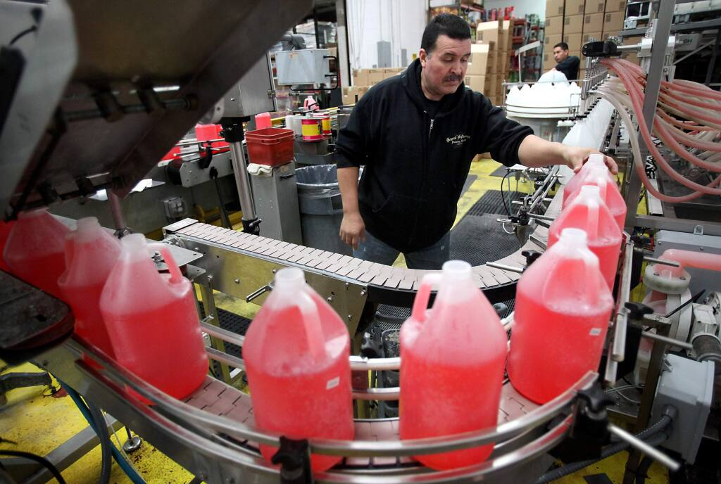 Eduardo Vega keeps bottles of General Hydroponics FloraBloom moving along the bottling line at the company's production facility in Sebastopol in 2012. (CHRISTOPHER CHUNG/ PD FILE)