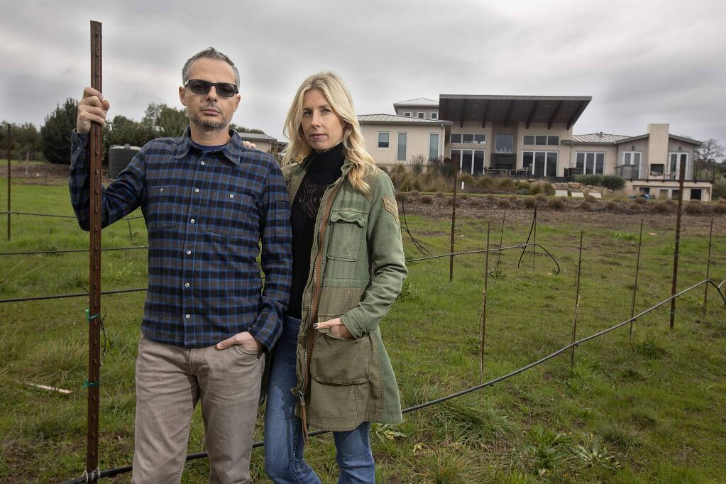 Jad and Stacie Elkhoury stand in front of their Sonoma home, which was spared from destruction in the Nuns fire, but suffered some smoke damage. The couple's insurance company recently dropped coverage for their vacation home in Truckee because it's in a heavy brush zone. (photo by John Burgess/The Press Democrat)