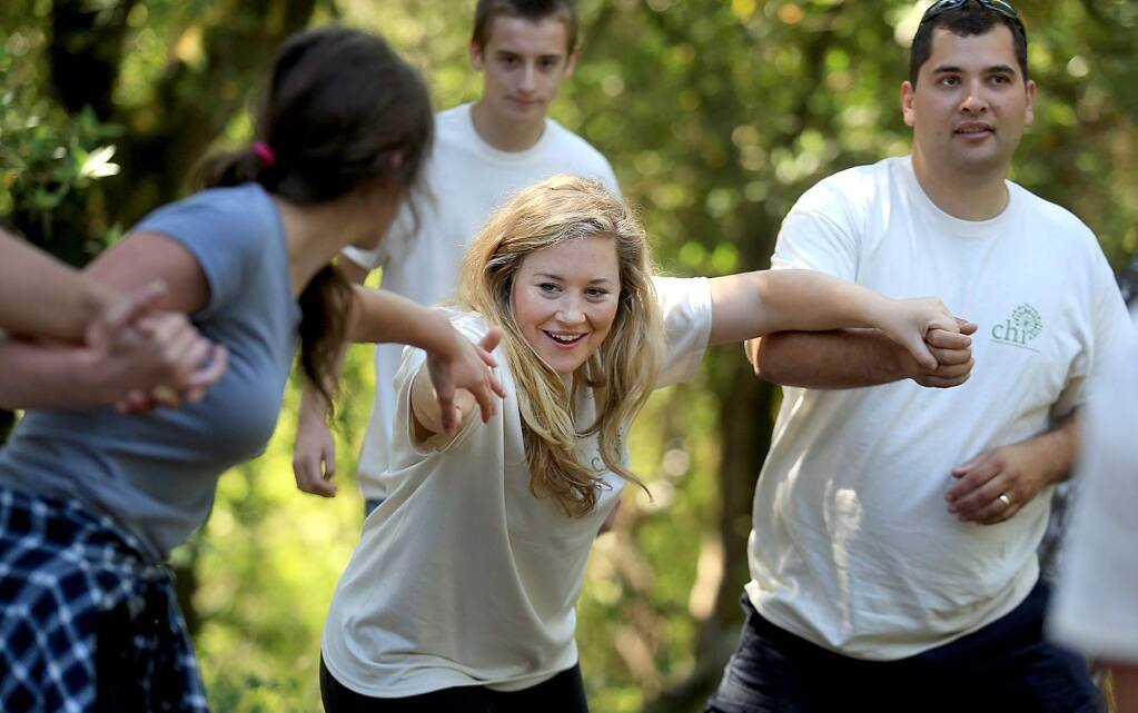 Lauren Taylor, middle, chaperone for Children's Humanitarian International, a nonprofit organization founded by SRJC board member Jordan Burns, right, takes part in a team building exercise at the Four Winds top course in Occidental, Thursday June 30, 2016. (Kent Porter / Press Democrat) 2016