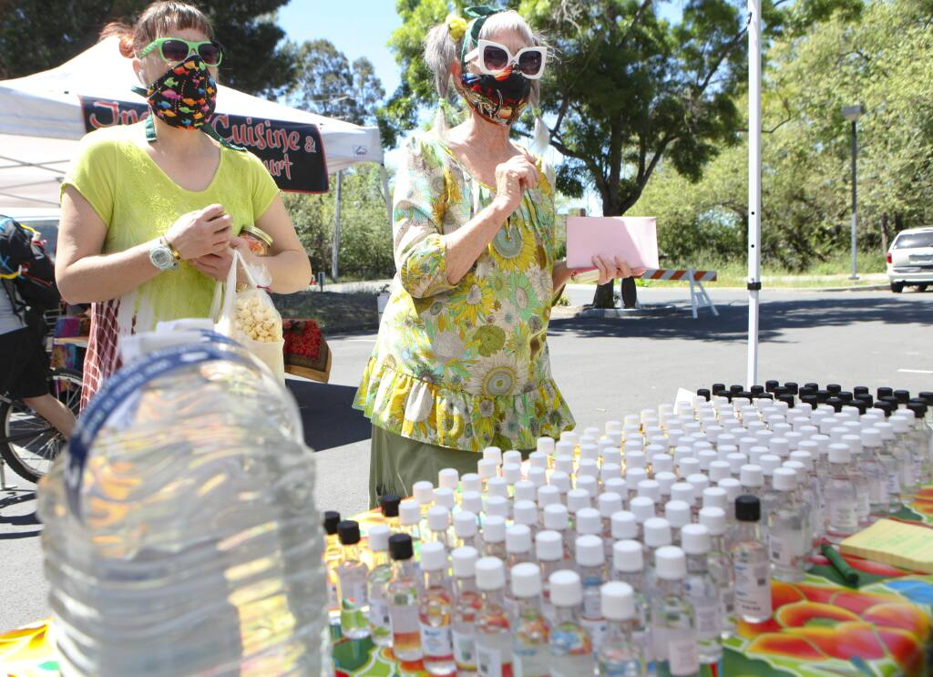 Petaluma, CA, USA. Tuesday, April 28, 2020._ Gretchen Lund (left)and her mother, Marilyn Lund picked up some hand sanitizer sold by Lightning Spirits at the Tuesday farmer's market on the east side of Petaluma. (CRISSY PASCUAL/ARGUS-COURIER STAFF)