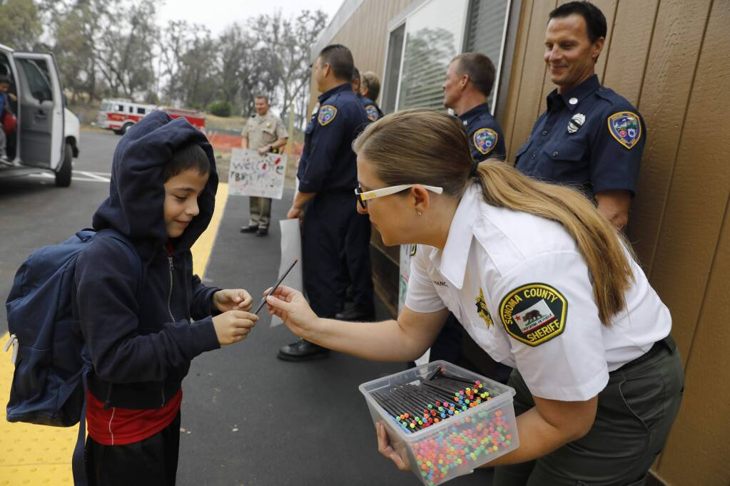 Karen Hancock, a community service officer with the Sonoma County Sheriff's Office hands a pencil to Victor Mazariego, 7, on the first day of class at the Redwood Adventist Academy campus after the Tubbs fire destroyed the school in October. Photo taken in Santa Rosa on Monday, August 20, 2018. (Beth Schlanker/ The Press Democrat)
