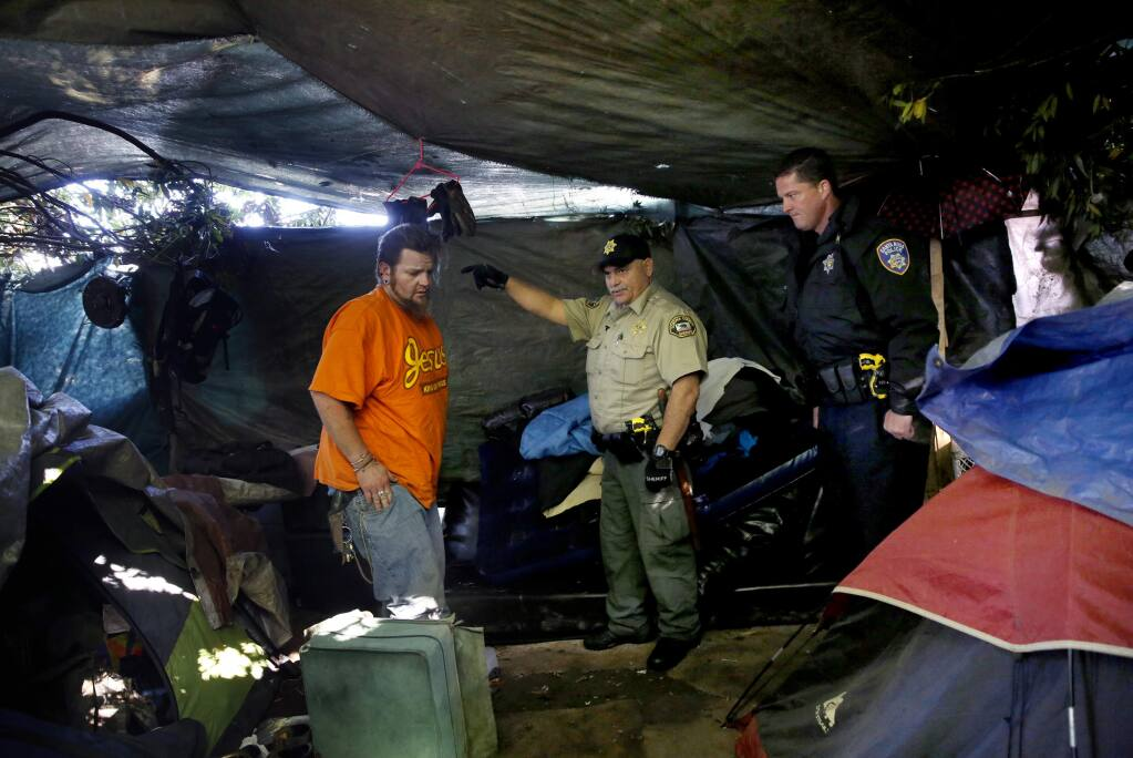 (From right) Santa Rosa police officer Jesse Cude and Sonoma County Sheriff's Deputy Jose Acevedo talk with Casey Easley in his tent as part of an effort by the Homeless Outreach Services Team at a homeless encampment on Mark West Creek near Almar Parkway in Santa Rosa, on Wednesday, April 8, 2015. (BETH SCHLANKER/ The Press Democrat) Sonoma Magazine