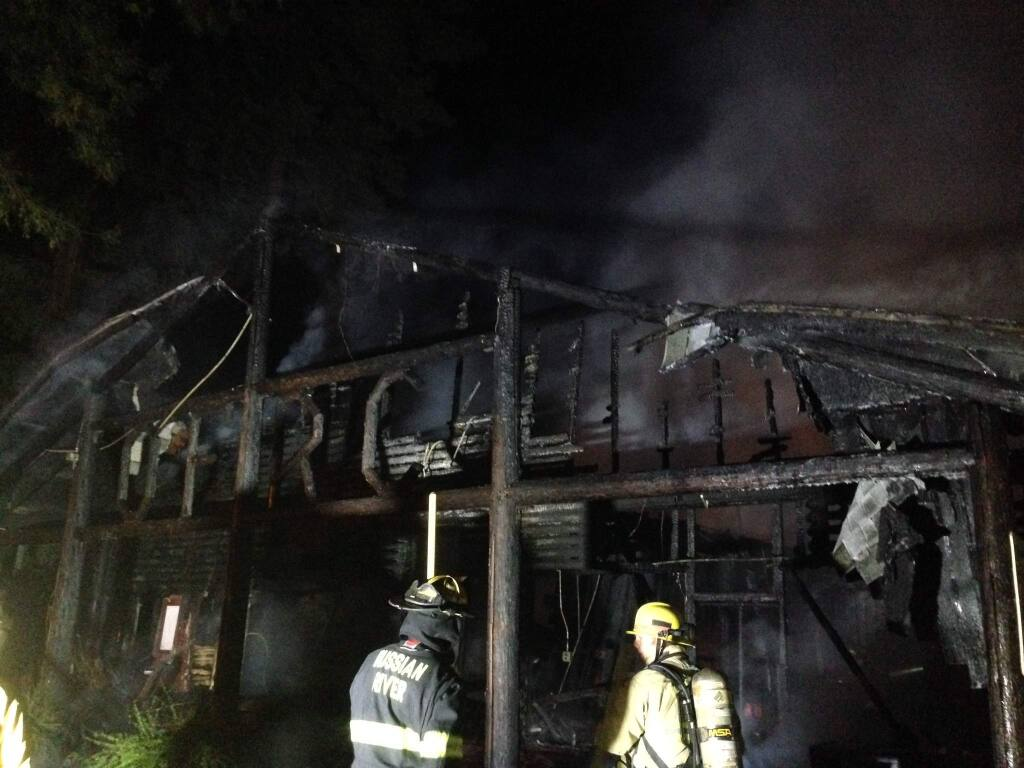 Firefighters work on the scene of a structure fire at Odd Fellows General Store, south of the Russian River outside Rio Nido on Tuesday night, Aug. 5, 2015 (Crista Jeremiason\The Press Democrat)