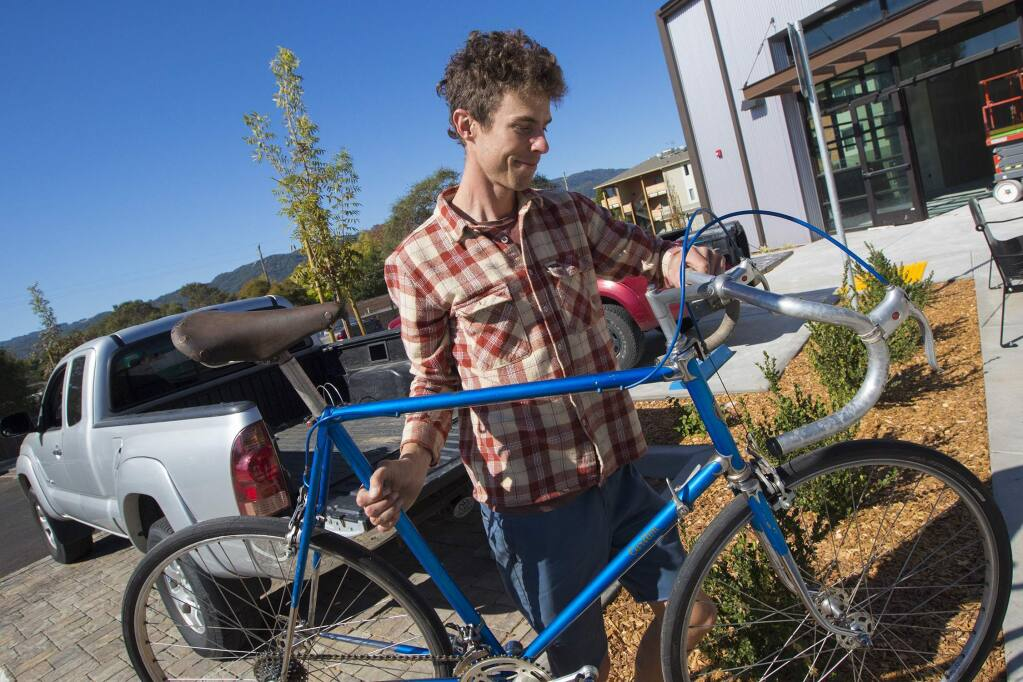 Teen Services store manager Adrian Palenchar brings some bicycles into the shop.(Photo by Robbi Pengelly/Index-Tribune)