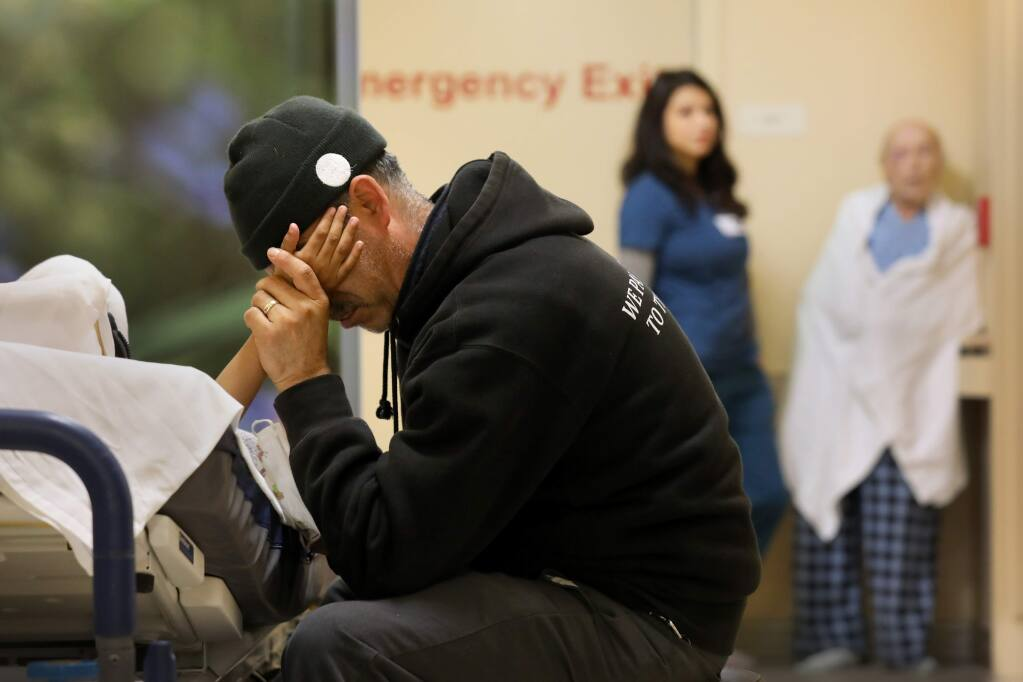 With no rooms available, Juan Sedano holds the hand of his son Daniel, 7, who lies in a hospital bed in the hallway of the Emergency Department at Santa Rosa Memorial Hospital in Santa Rosa on Tuesday, Dec. 3, 2019. (BETH SCHLANKER/ PD)