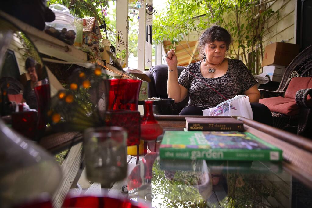 PHOTO: 2 BY CHRISTOPHER CHUNG/ THE PRESS DEMOCRAT -Laura Blackmore does needlepoint on the porch outside her room at Stony Point Commons in Santa Rosa. Blackmore, who was homeless for two years, has lived at the facility for six years.