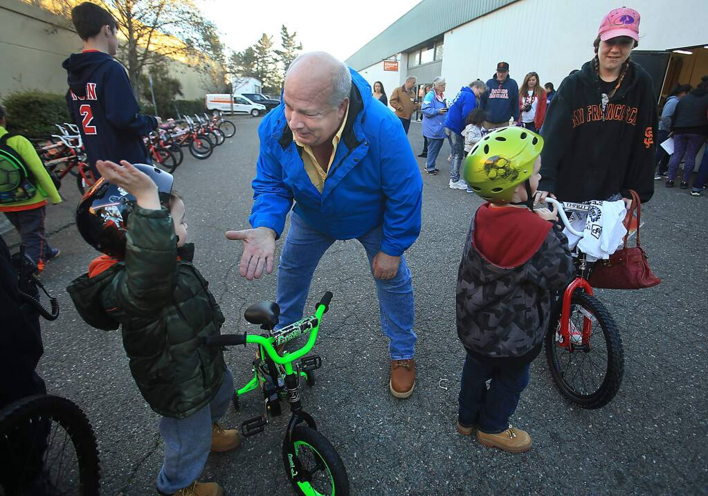 Innovative Screen Printing and Embroidery owner Mark Pippin gets a high five from Ayden Bishop, 4, as his brother Jeremiah Bishop, 6, waits with their mother Nichole McCarty after the two received free bikes from Pippin in Rohnert Park, Friday Dec. 16, 2016. (Kent Porter / The Press Democrat) 2016