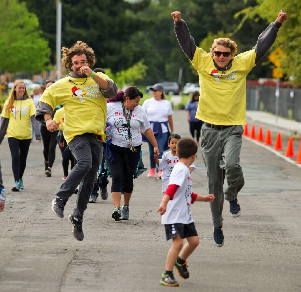 Tyler Coxey, left, and Hamk Martin skip across the finish line in the 2018 Human Race in Santa Rosa. (photo by John Burgess/The Press Democrat)