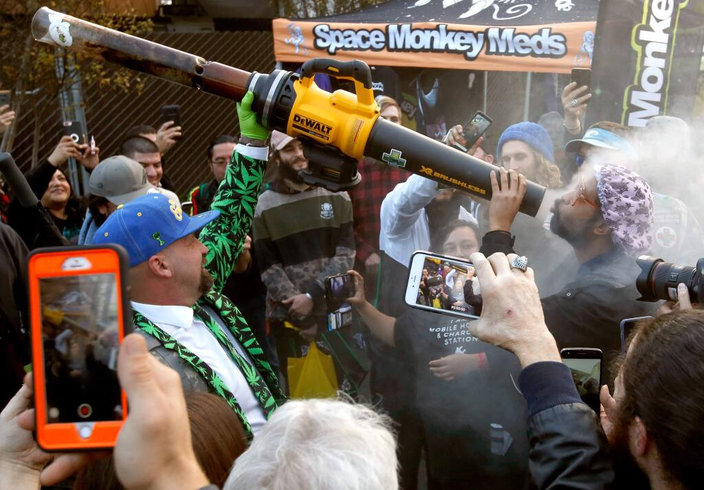 Scott Martin, left, blazes up his Kush Cannon, a giant marijuana pipe connected to a leaf blower, for attendees during the Emerald Cup at Sonoma County Fairgrounder in Santa Rosa, California, on Saturday, December 15, 2018. (Alvin Jornada / The Press Democrat)